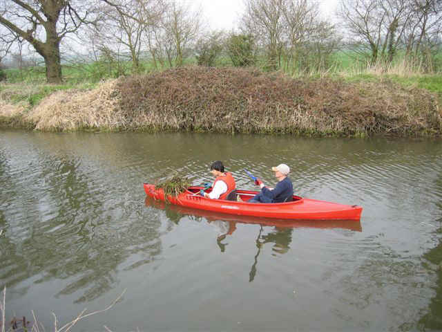 A voluntary weed picking crew with a bundle of weed on the foredeck in Ricketts Lock Cut, April 2005